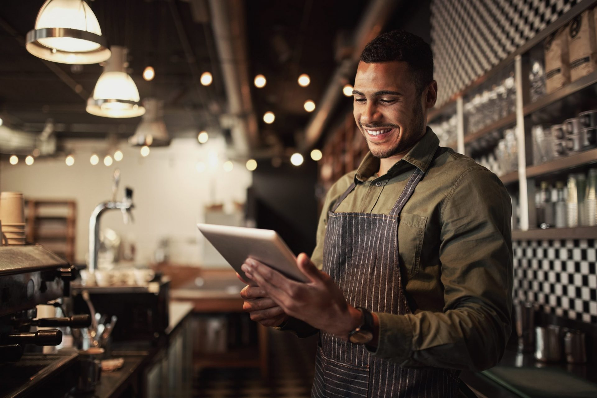 Cheerful black cafe owner behind counter using digital tablet