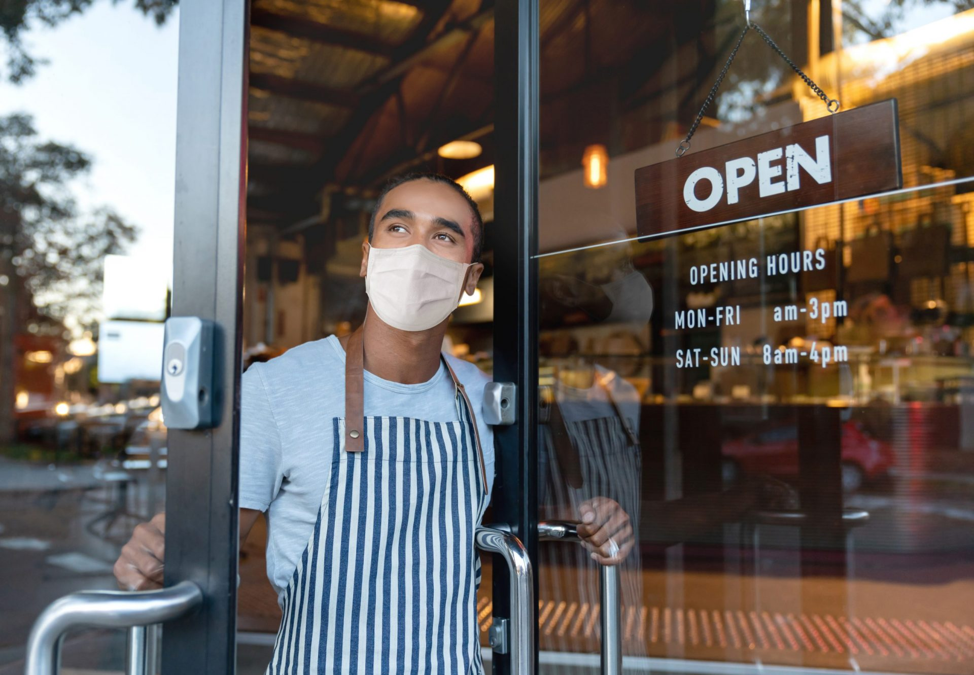 Business owner opening the door at a cafe wearing a facemask to avoid the spread of coronavirus – reopening after COVID-19 concepts