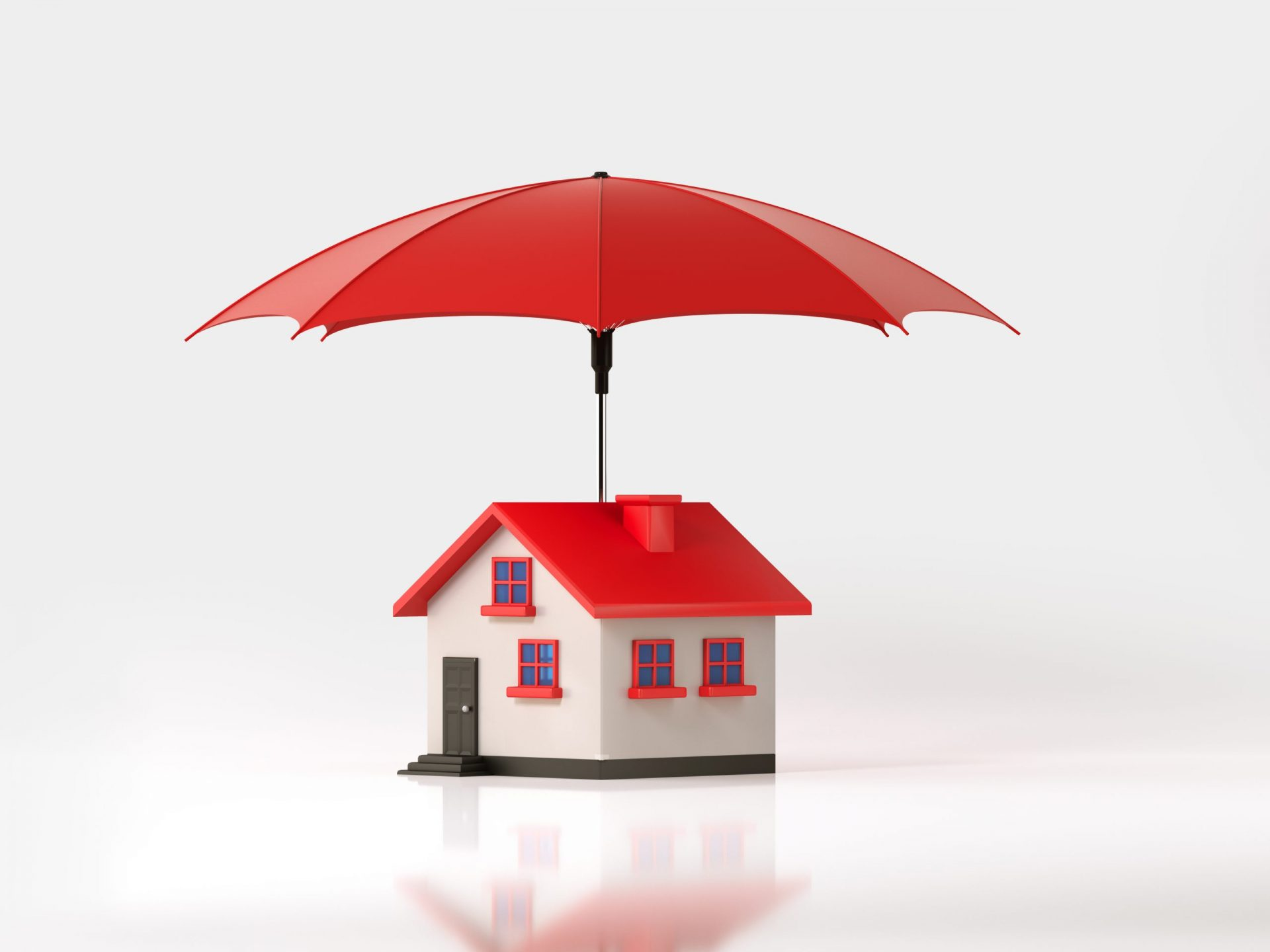 Red umbrella is protecting a toy house on white background. Horizontal composition with selective focus and copy space. Insurance and real estate concept.