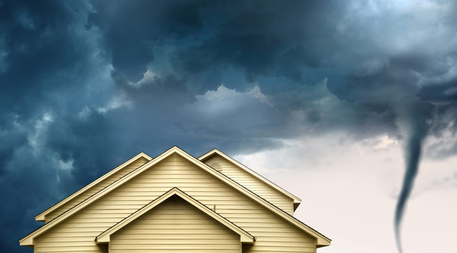 close up rooftop of a wooden house over stormy clouds sky and approaching tornado.